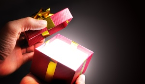 Hands opening a red gift box with ribbon in shadow