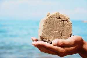 Close up on hands holding Home made from sand. House on seashore. Summer holiday, vacation, postcard, background.  Real estate investment concept