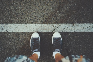 View of feet of man in white socks and gumshoes standing near grunge white line on gray asphalted road, ready to pass