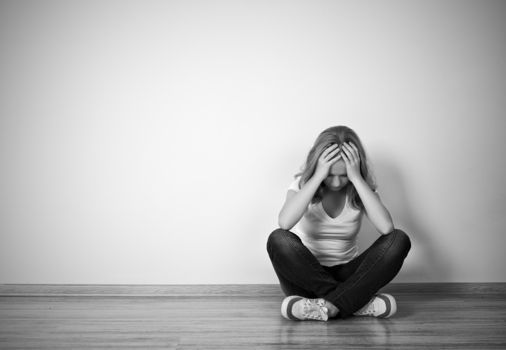 girl sits in a depression on the floor near the wall