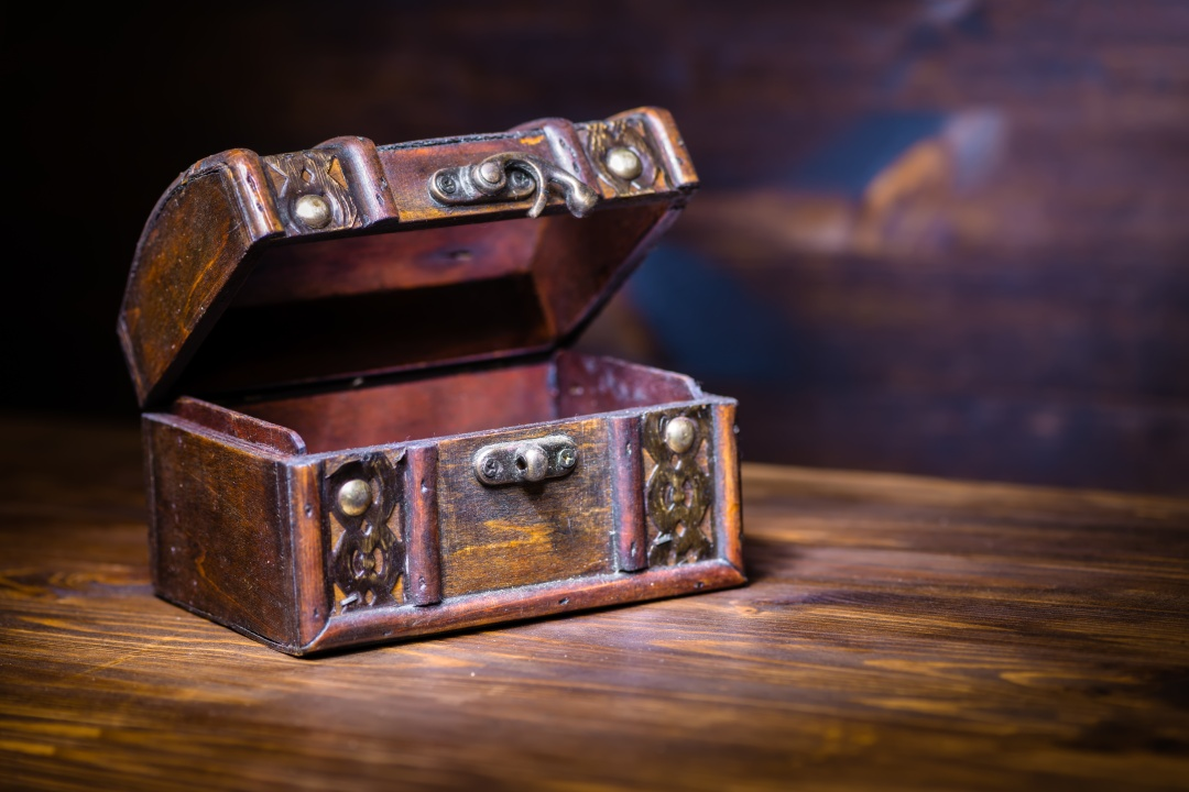 beautiful retro chest with open lid on wooden background with pl