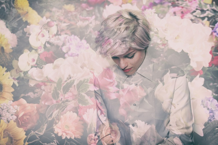 Double exposure of beautiful thoughtful girl portrait and colorful flowers