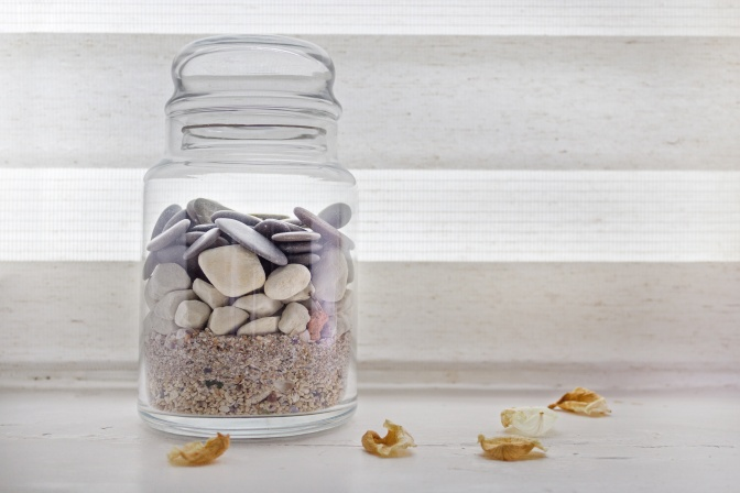 Jar with sand and rocks from travels on a window